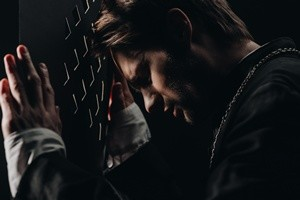 young tense catholic priest with closed eyes leaning on confessional grille in dark with rays of light